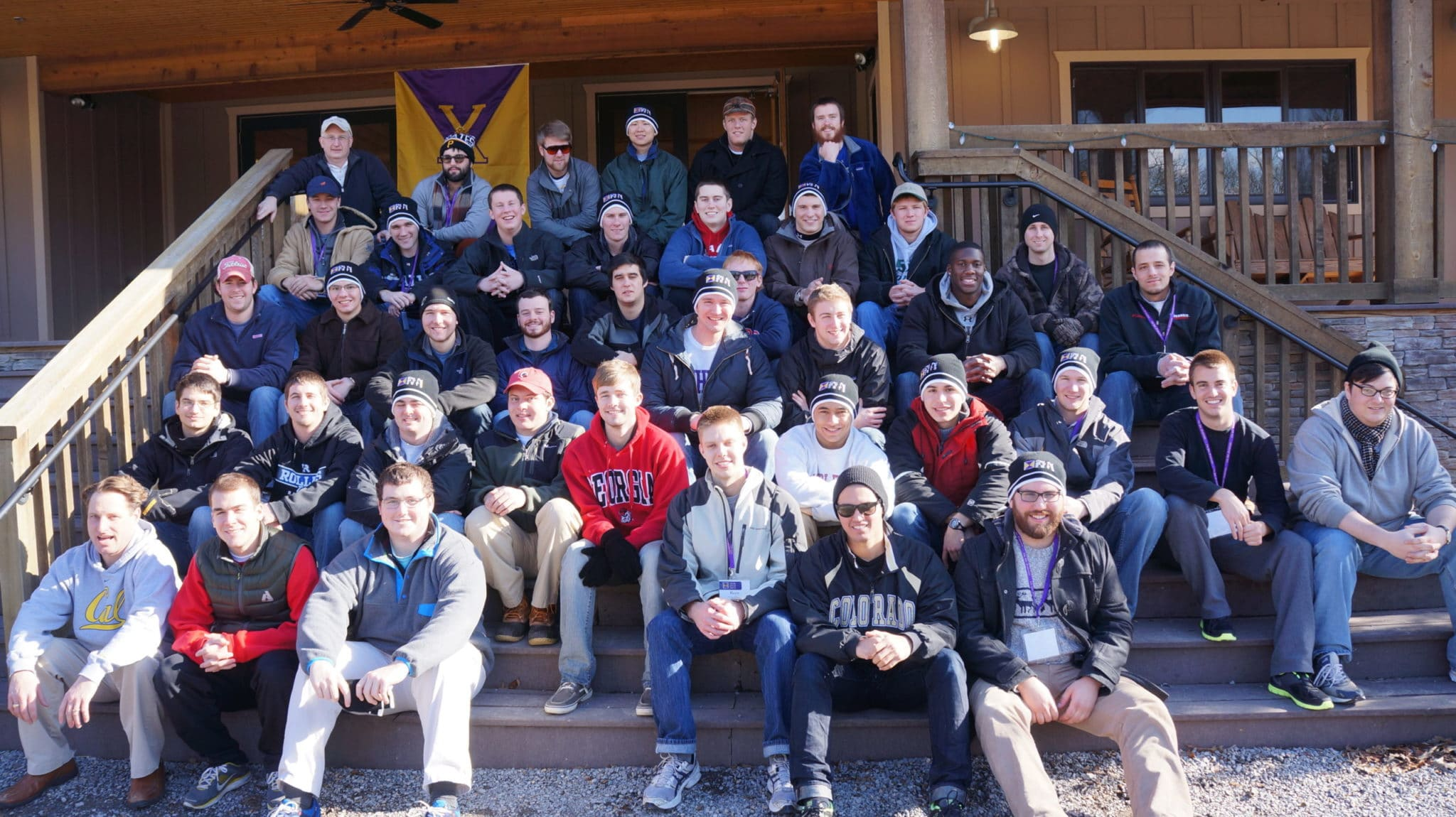 Fraternity sitting on steps posing for photo